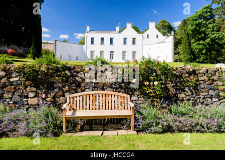 Garden seat in a formal garden beside a large white house. - Stock Photo
