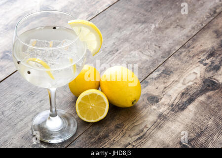 Glass of gin tonic with lemon on wooden background - Stock Photo