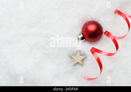 Overhead of Christmas background with decorative red bauble, ribbon swirl and wooden star partially buried in artificial - Stock Photo