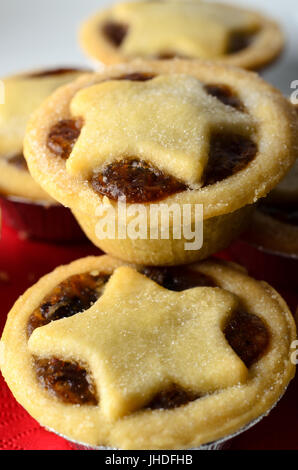 Close up of Christmas mince pies with star shaped pastry toppers, piled on a white plate with crumbs; a red napkin. - Stock Photo