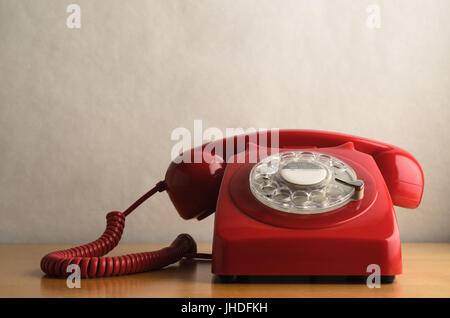 Eye level shot of a retro red telephone (British circa 1960s to 1970s) on a light wood veneer desk or table with - Stock Photo
