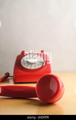 Eye level shot of a retro red 1960s to 70s British style telephone, with receiver off the hook and in close up foreground. - Stock Photo