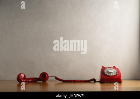 Eye level shot of a retro red dial up telephone on a light wood veneer desk or table with handset taken off the - Stock Photo
