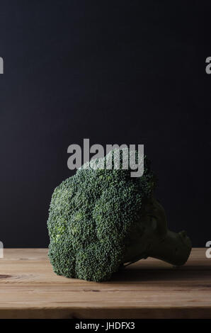 A head of dark green broccoli with stalk intact, on wooden planked table against black chalkboard background.  Moody - Stock Photo
