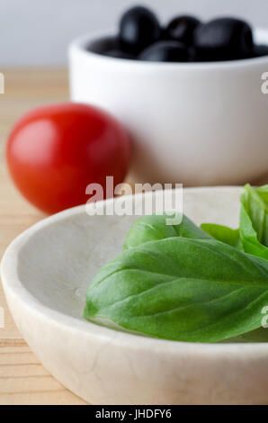 Serving dish of freshly picked green basil leaves in foreground with red tomato and black olives in white bowl in - Stock Photo