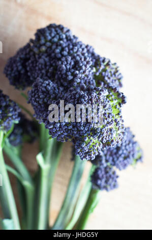 Close up of the head of a stalk of purple sprouting broccoli on a light wooden chopping board. - Stock Photo