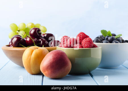 Eye level shot of various fresh fruits, in separate bowls and on light blue painted wood plank table with copy space - Stock Photo