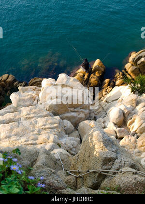 top view of fisherman sitting on rocks with fishing rods in Ulsan - Stock Photo