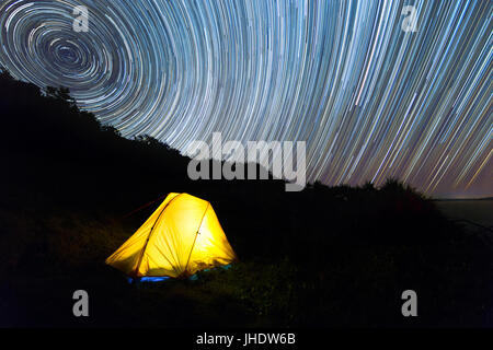 A yellow hiking tent illuminated with light under a beautiful night sky star trail. - Stock Photo