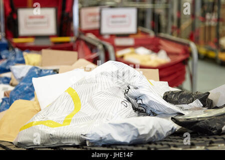 mailing postal bags on conveyor belt at royal mail delivery office - Stock Photo