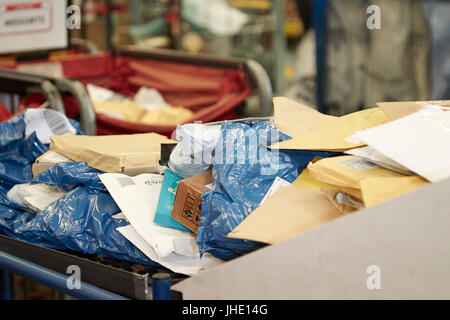 mailing postal bags small parcels and envelopes on conveyor belt at royal mail delivery office - Stock Photo