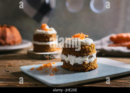 Mini carrot cake, stuffed with cream cheese, on blue concrete dish, on rustic wood - Stock Photo