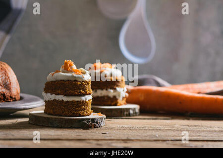 Mini carrot cake, stuffed with cream cheese, on rustic wood plate, close up - Stock Photo