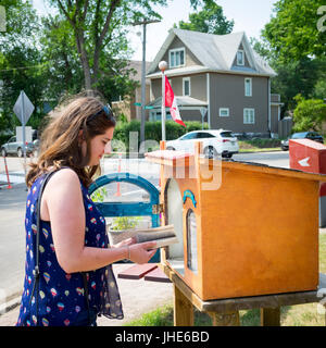 A pretty brunette woman uses a Little Free Library book exchange box in Saskatoon, Saskatchewan, Canada. - Stock Photo