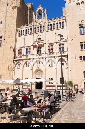 Tourists sitting at outdoor restaurant before the Bishop's Palace, Narbonne, Occitanie, France - Stock Photo