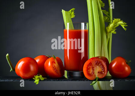 Tomato juice or cocktail bloody Mary with tomatoes and celery sticks on a dark background - Stock Photo