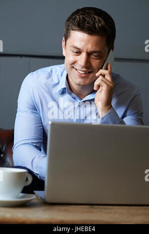 Businessman Talking On Mobile Phone Working On Laptop In Internet Cafe - Stock Photo