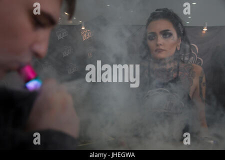 A man smokes electronic cigarettes at the 'Vape Show' exhibitionin  in Moscow, Russia - Stock Photo
