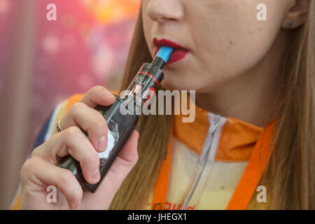 A woman smokes electronic cigarettes at the 'Vape Show' exhibitionin  in Moscow, Russia - Stock Photo
