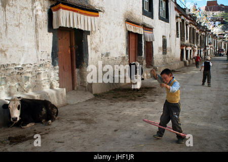 Two children play in the streets of the old town of Gyantse. Gyantse village, Tibet, China. - Stock Photo