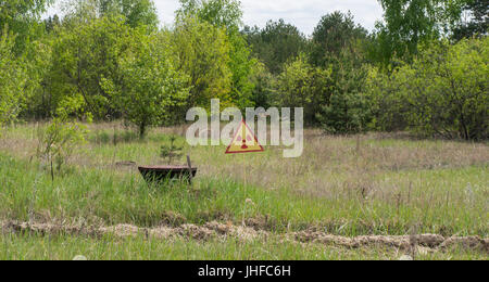 A sign warning of radiation and contamination in Chernobyl - Stock Photo