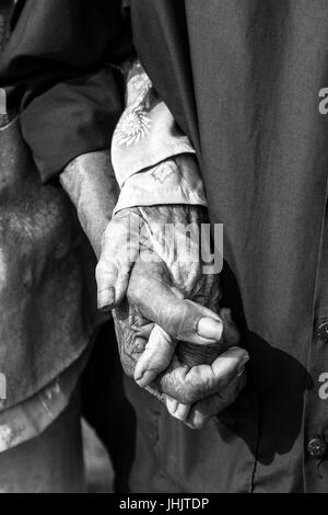 Black and white of everlasting love - old couple holding hands - Stock Photo