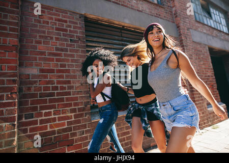 Multiracial group of friends walking down the city street. Three young women walking outdoors on road. - Stock Photo