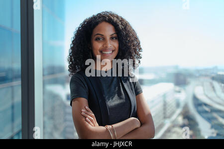 Closeup of a smiling businesswoman standing by the window of her office. Young woman with curly hair and arms crossed - Stock Photo