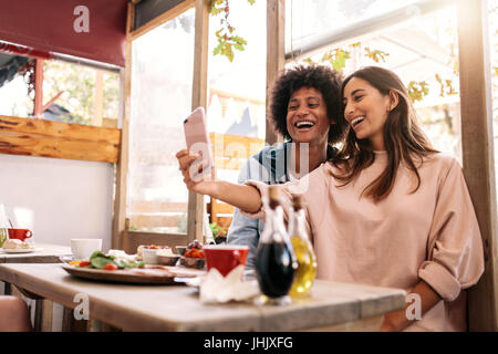 Cheerful woman taking selfie with her friend at cafe. Couple having fun using smartphone at coffee shop - Stock Photo