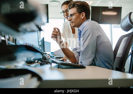 Side view of a mature businessman and businesswoman working together on desktop computer. Two business professionals - Stock Photo