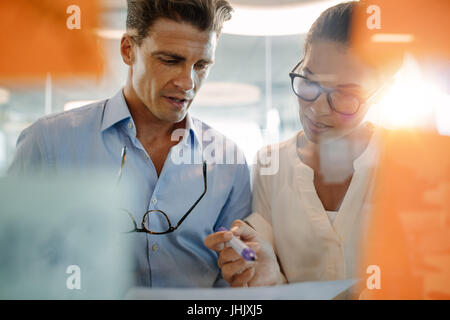 Two business professionals standing behind the glass wall with sticky notes and discussing. Colleagues brainstorming - Stock Photo