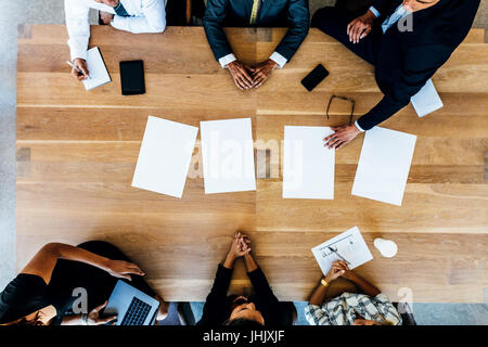 Top view of business people sitting around a table with blank sheets. Multi ethnic business professionals in meeting. - Stock Photo