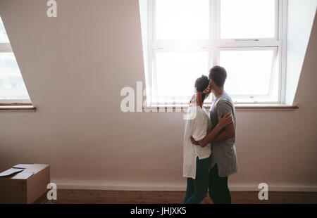Loving young couple moving in a new apartment. Man and woman standing together with boxes on floor. - Stock Photo