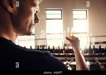 Male brewer testing craft beer at brewery factory. Young man examining the beer sample glass during manufacturing. - Stock Photo