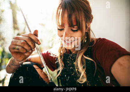 Close up of beautiful young caucasian woman artist with paint brush. Female painter holding brush and smiling. - Stock Photo