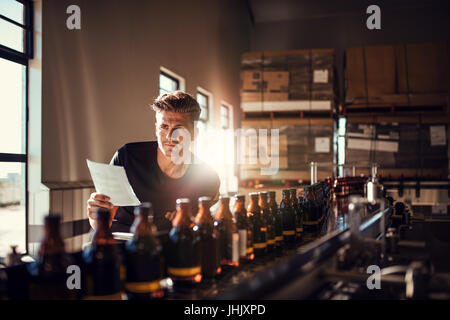 Young man supervising the process of beer manufacturing on brewery factory. Factory worker checking the process - Stock Photo