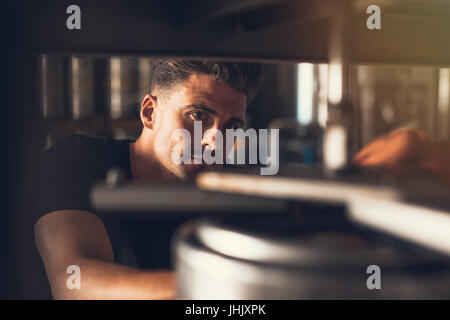 Brewer working on beer production line at brewery. Man working at alcohol manufacturing factory. - Stock Photo