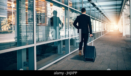 Rear view of young businessman walking outside public transport building with luggage. Business traveler pulling - Stock Photo