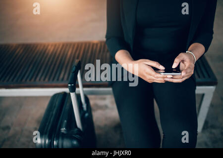 Cropped shot of young businesswoman sitting on bench with suitcase and using mobile phone. Female waiting in public - Stock Photo