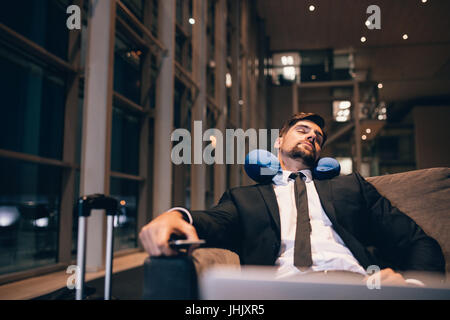 Traveler waiting at airport after flights delays and cancellations. Businessman asleep in airport lounge. - Stock Photo