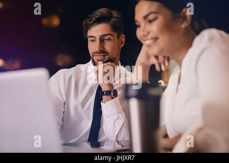 Business man and woman sitting at table and looking at laptop. Business people waiting at airport lounge using laptop - Stock Photo