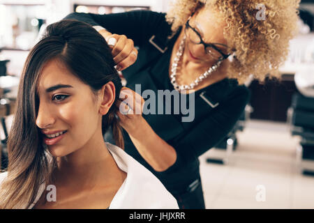 Closeup of a woman getting a stylish hairdo done at salon. Professional hair stylish pinning up the hair in stylish - Stock Photo