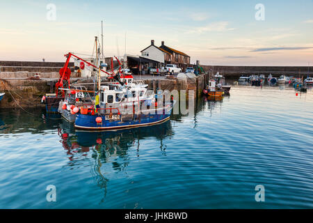 2 July 2017: Lyme Regis, Dorset, England, UK - Fishing boats in the harbour at sunset. - Stock Photo