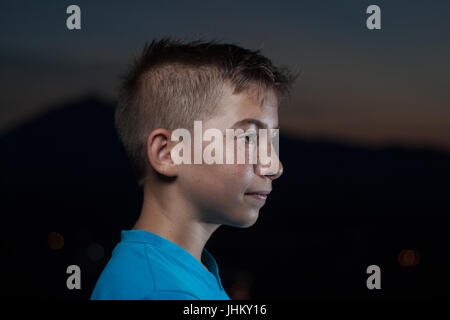 portrait of young teen boy looking sideways at night - Stock Photo
