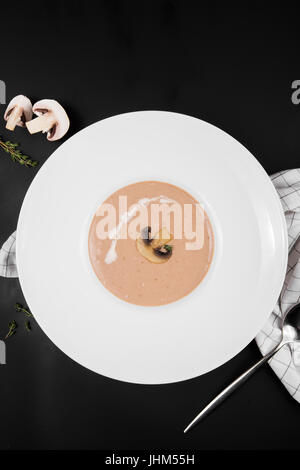 Mushroom cream soup in a white bowl with seasoning on black background, top view - Stock Photo