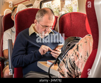 A middle aged man using his mobile phone on a train in England. UK. - Stock Photo