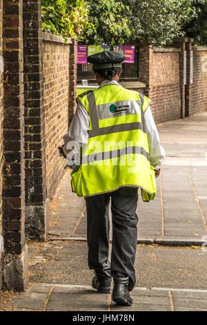 A London Borough of Ealing traffic warden walking down an Ealing, London street, England, UK. - Stock Photo