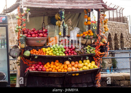 A stall loaded with a variety of fruits for making juice in an outdoor market in Acre, Israel. - Stock Photo