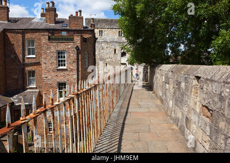 A young girl stands on a scenic section of the medieval walls of the historic city of York at Monk Bar. - Stock Photo