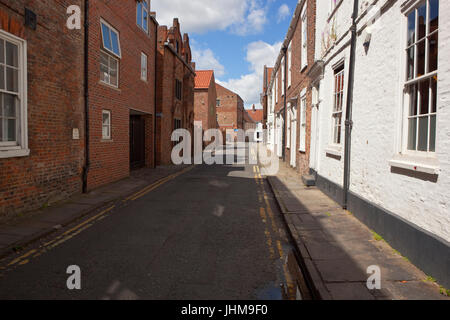 an old york city street with houses and businesses under a summer blue sky - Stock Photo